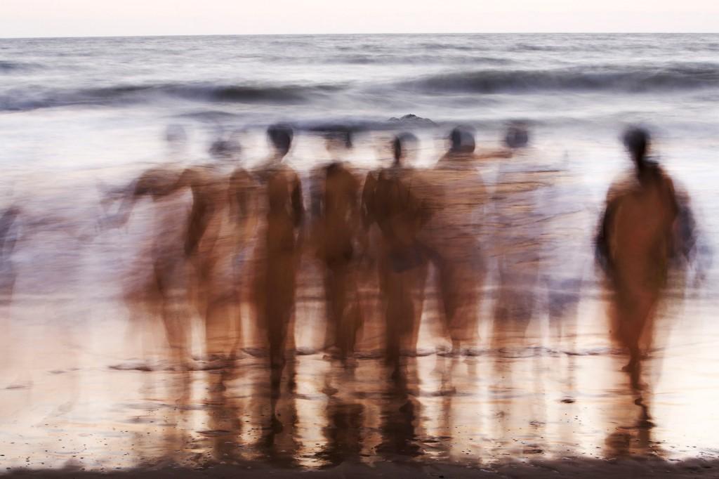 Indien, Karnataka, Gokarna, Stadtstrand, Pilger am Meer, heiliger Ort, straeuen Asche von Verstorbenen ins Wasser, Pujas, abend, Daemmerung, Bewegung