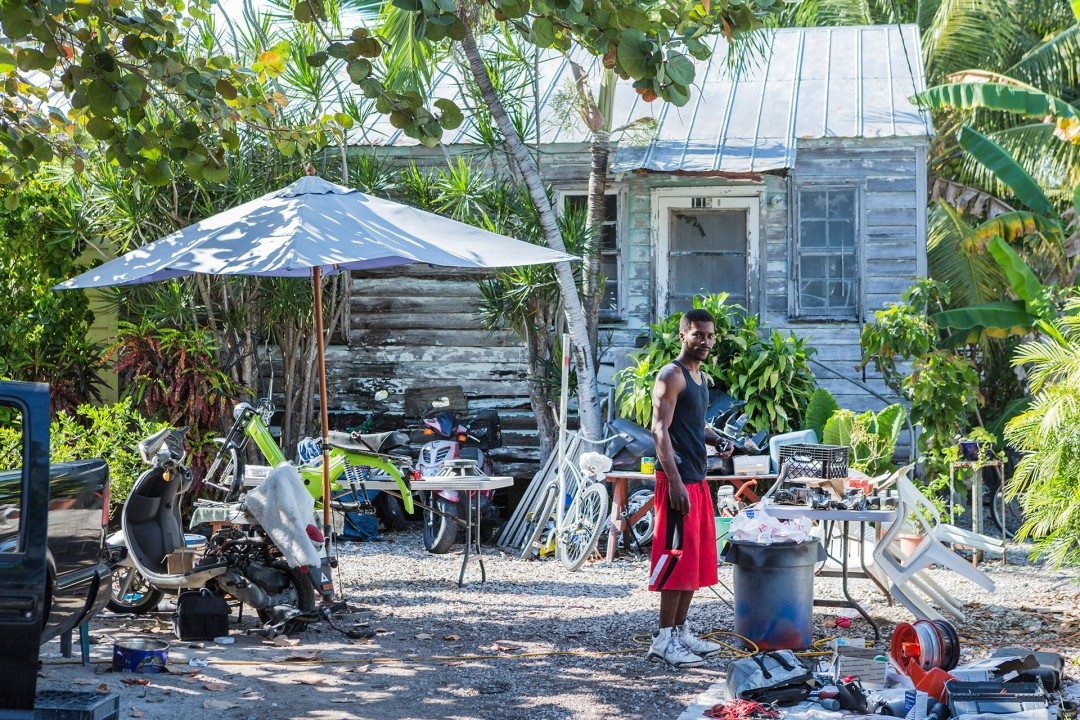 Reise Travel laif creative USA Amerika, United States of America, Florida, Florida Keys, Key West  Bahama Village einfaches Holzhaus Conch House Mann Repariert Motorroller