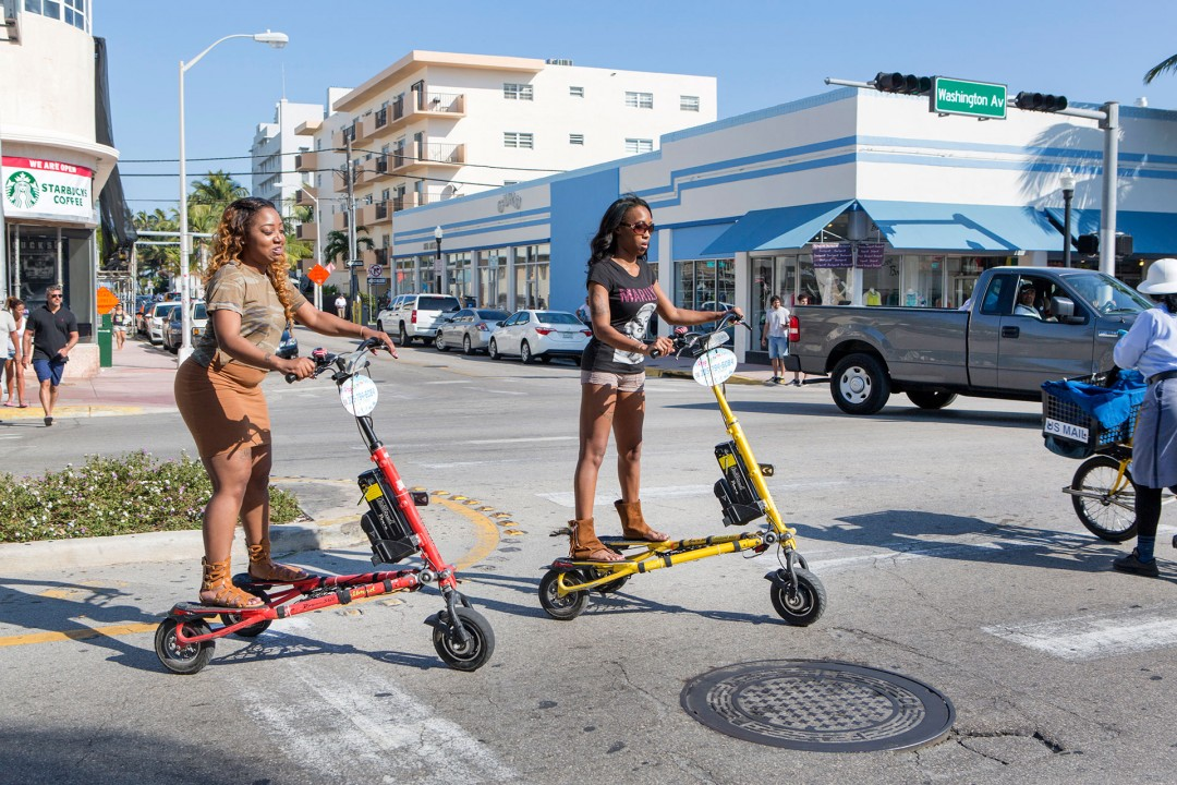 USA, Amerika, United States of America, Florida, Miami, South Beach, Art Deco District, 1001 Washington Ave, zwei Frauen auf elktrischen Drei Raedern, E- Bike, E Fahrrad, Dreirad