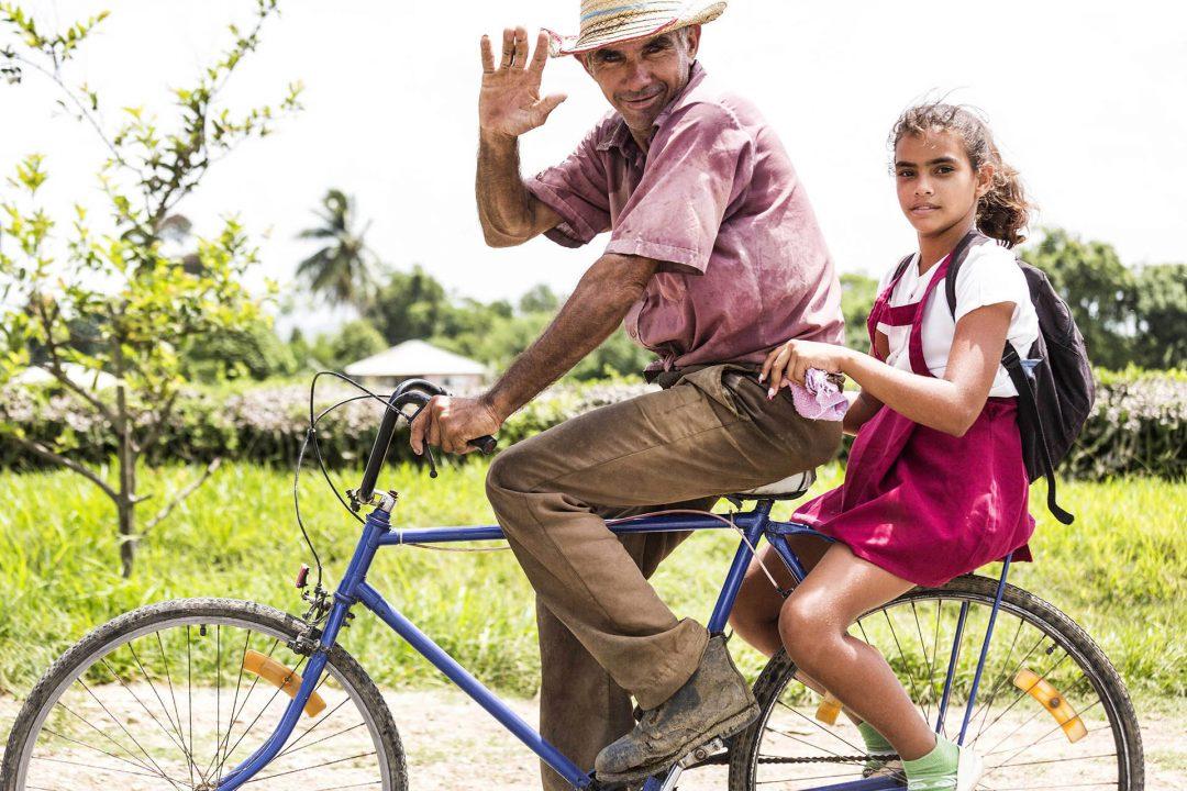 Antillen, Karibik, Cuba, Kuba, Republica de Cuba, Sozialismus, Holguin, Mann, Maedchen, Fahrrad, winkt, Schuluniform
