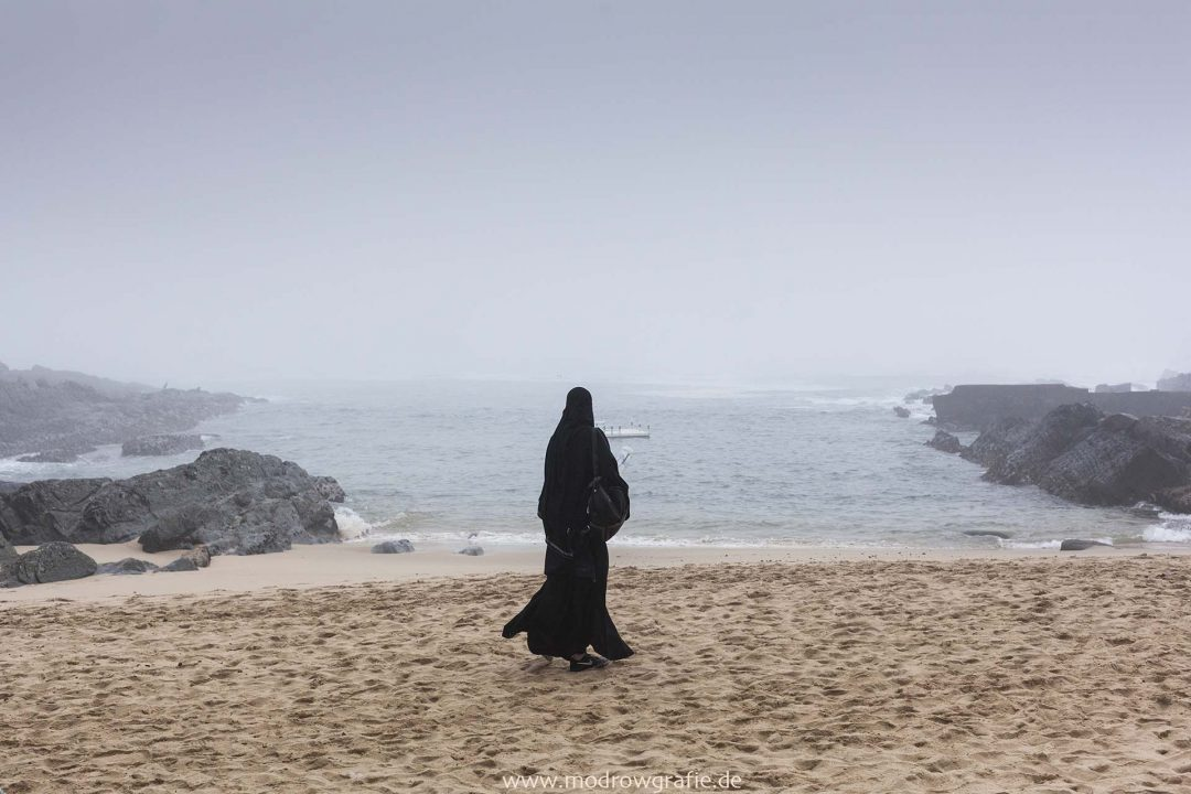 Suedafrika, Afrika, Westkap, Garden Route, Tsitsikamma National Park, Felsen, Kueste, Meer, Bewegung, Brandung, Engl: Southafrica, Western Cape, Landscape, Gardenroute, Travel, Storms River mouth, coast, ocean, rocks, Muslim Woman on the beach,