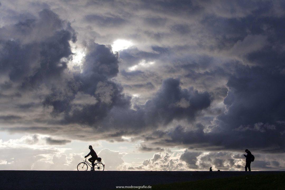 Europa, Deutschland, Niedersachsen, Ostfriesland,Norddeich, Radfahrer, Wolken, Himmel ueber der Nordsee, Deich